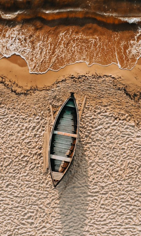 brown and white boat on brown sand wallpaper