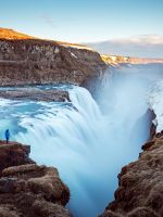person standing on cliff near large waterfalls und... wallpaper