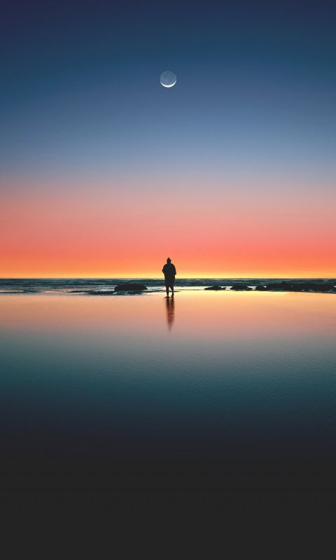 silhouette of man standing on seashore wallpaper