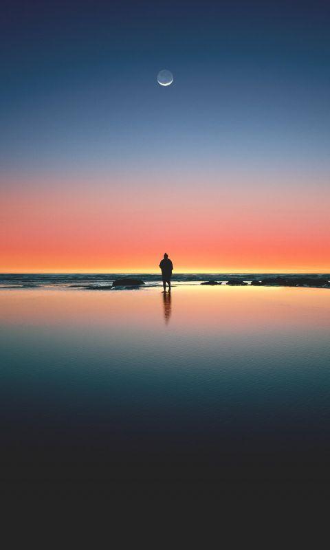 silhouette of man standing on seashore wallpaper
