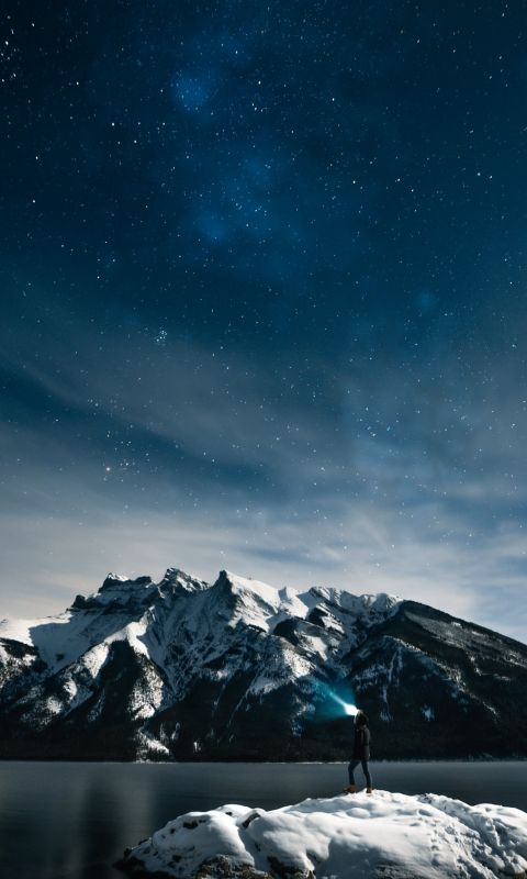 person standing on rock at night wallpaper