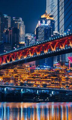lighted bridge across calm water wallpaper