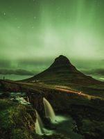 waterfalls near mountain taken under green sky wallpaper