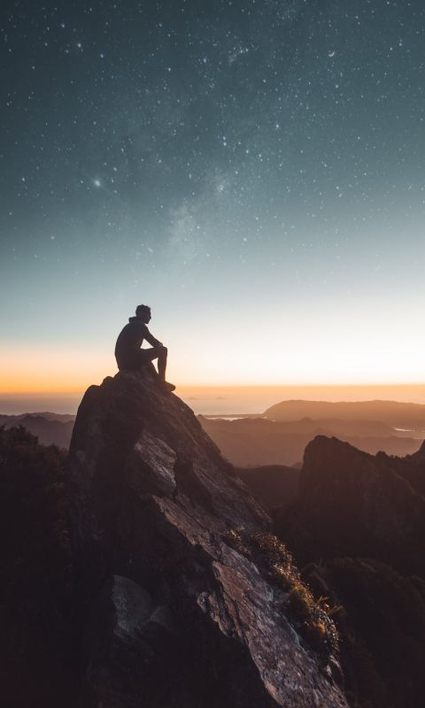 silhouette of person sitting on rock formation dur... wallpaper
