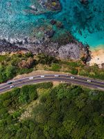 aerial view of road near body of water during dayt... wallpaper
