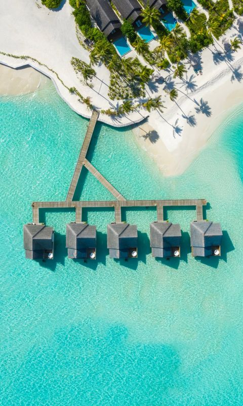 brown huts on body of water in aerial photography wallpaper