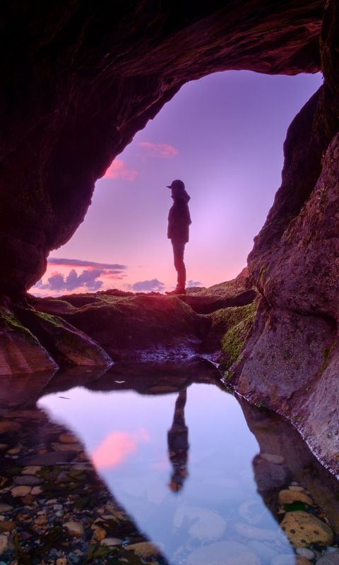man standing in front of cave wallpaper