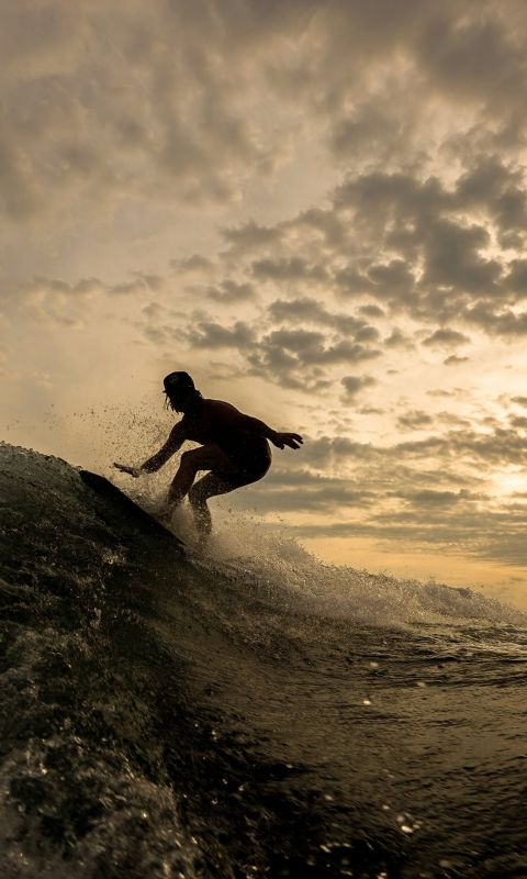 silhouette of person riding on surfboard wallpaper