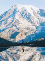 man walking near glacier mountain during day wallpaper