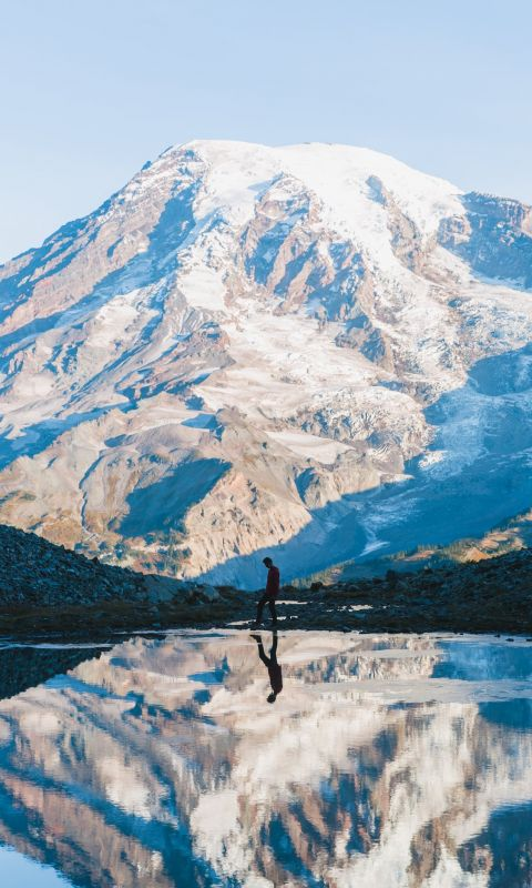 man walking near glacier mountain during day wallpaper
