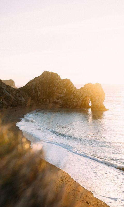 rock monolith beside calm body of water wallpaper