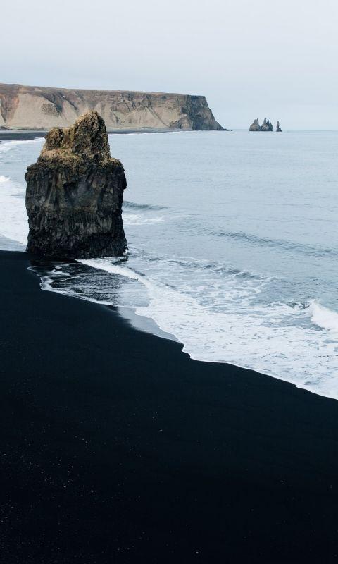 brown monolith rock on seashore wallpaper