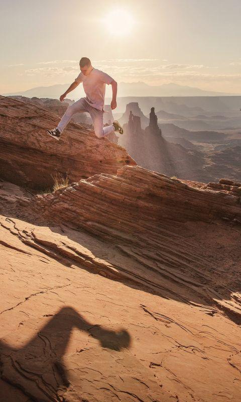 man jumping under sunlight wallpaper