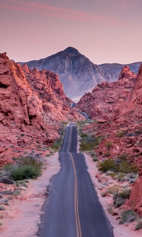 photo of empty road between rock formations wallpaper