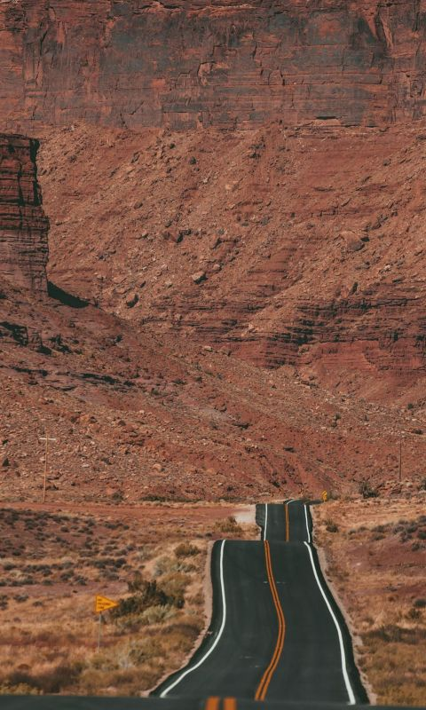 white car on road near brown rock formation during... wallpaper