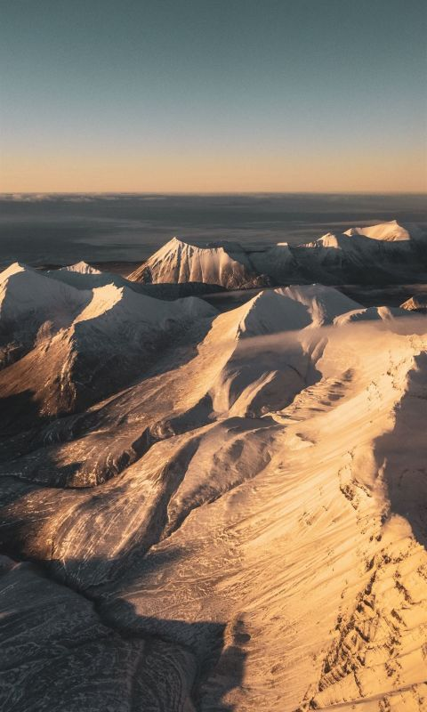 brown and white mountains under blue sky during da... wallpaper