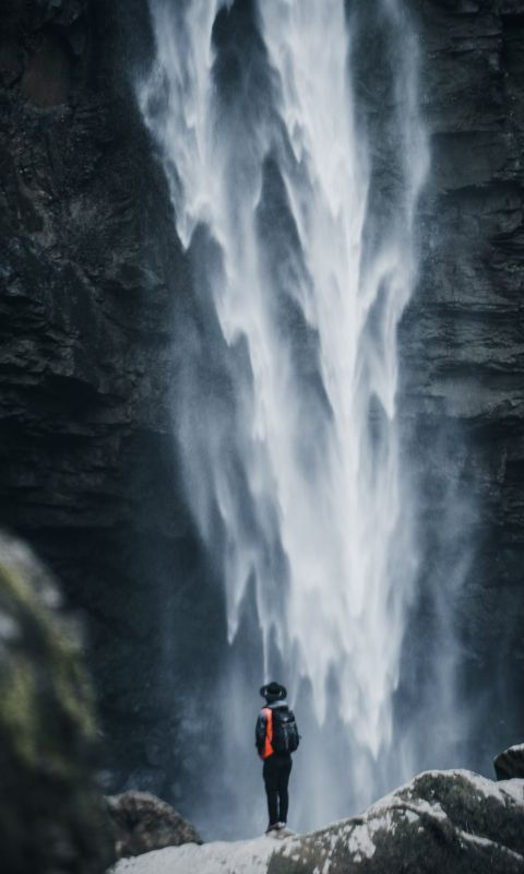 man standing near waterfalls wallpaper