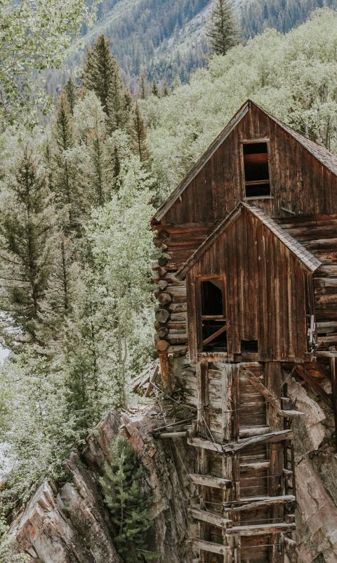 brown wooden house on rock formation near green tr... wallpaper
